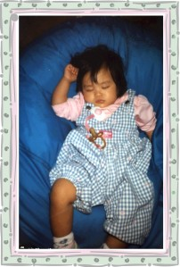 Asian baby girl asleep on a bean bag chair