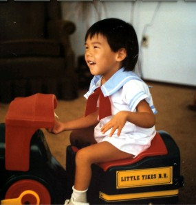 Asian toddler happily sitting on a riding toy
