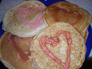 plate of pancakes with heart outline in the middle