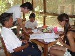 Volunteers helping Bribri students with homework
