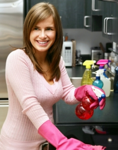 Cheerful woman dressed in pink smiles as she cleans.