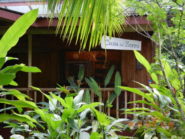 "House semi-hidden by tropical plants with the sign ""Casa Zorro"""