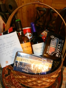Basket full of tea, wine, snacks, etc with welcome note