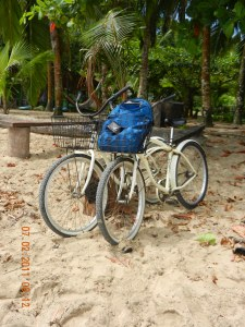 Two bikes with backpack parked on the beach