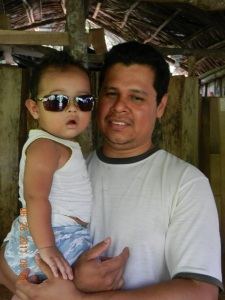 Man holding young baby wearing sunglasses.