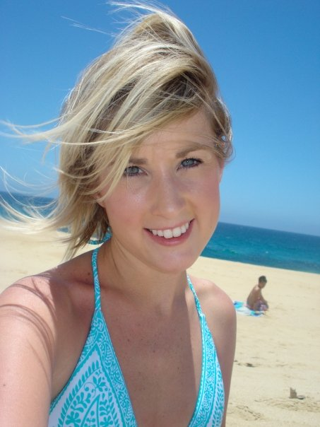 Blonde haired girl in bathing suit on the beach.